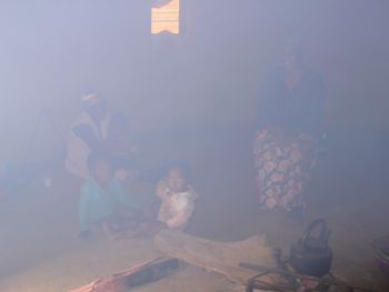Blick in die runde Zuluhütte mit Großmüttern und Kleinkindern